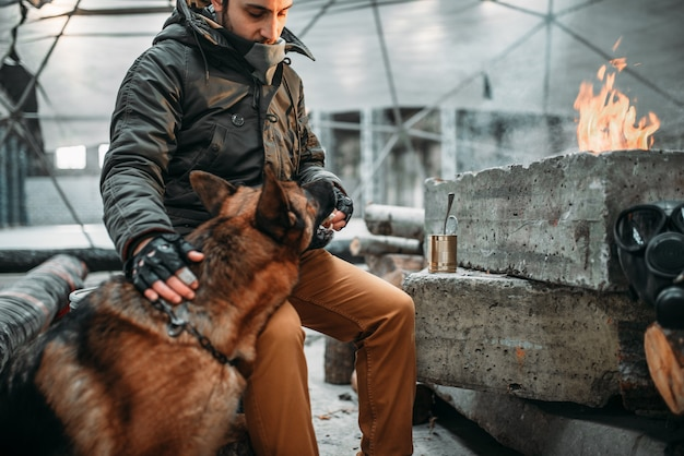 Stalker, soldaat na de apocalyps die een hond voedt. post apocalyptische levensstijl op ruïnes, dag des oordeels, dag des oordeels