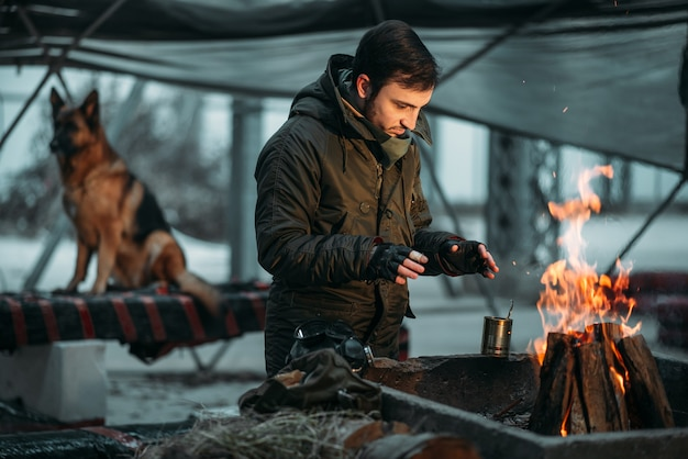 Stalker verwarmt zijn handen in vuur en vlam, hond. post apocalyptische levensstijl op ruïnes, dag des oordeels, dag des oordeels