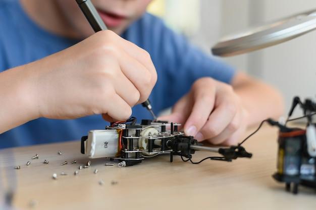 Stam onderwijs concept jonge uitvinder assembleren radiobesturing robot close-up diy robot in de wetenschap