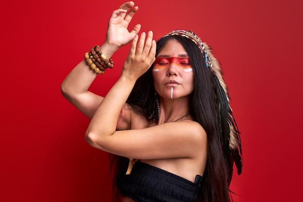Stammen indische vrouw die tijdens ritueel danst die sjamaankostuum draagt dat over rode muur wordt geïsoleerd