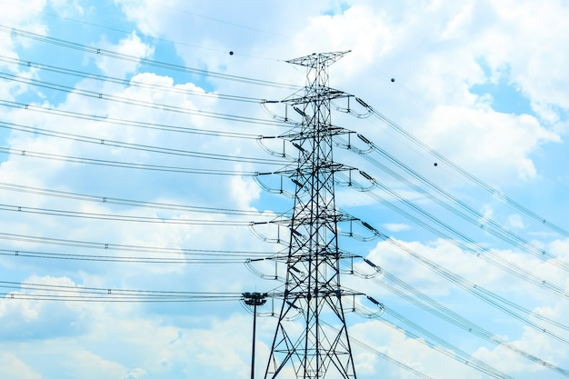 Stand alone van gigantische elektriciteitspaal alleen met de kabel met de blauwe lucht