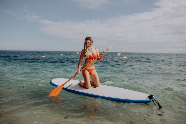 Stand-up paddle board vrouw paddleboarding op sup blij staan op paddleboard in water.