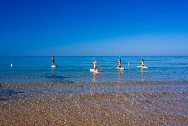 Stand-up paddle-boarding. vrolijke groep vrienden traint sup-bord in de middellandse zee op een zonnige ochtend op het strand van realmonte, sicilië. italië