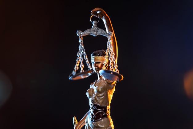 Standbeeld godin van rechtvaardigheid op donkere achtergrond