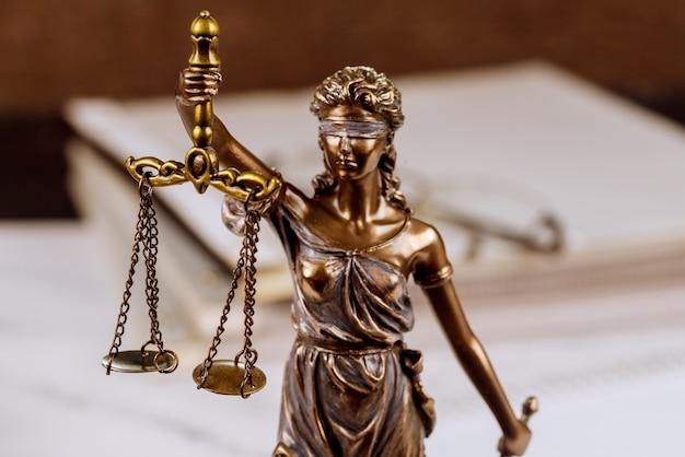 Standbeeld justitie schalen wet advocaat stapel onvoltooide documenten op bureau