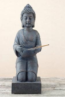 Standbeeld van boeddha met wierookstokje
