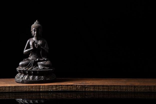 Standbeeld van boeddha zit in meditatie met zwarte kopie ruimte