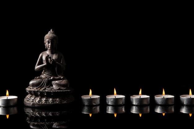 Standbeeld van boeddha zittend in meditatie, kaars lijn met zwarte kopie ruimte