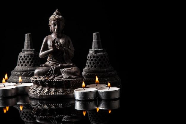 Standbeeld van boeddha zittend in meditatie, kaarsen, met zwarte kopie ruimte