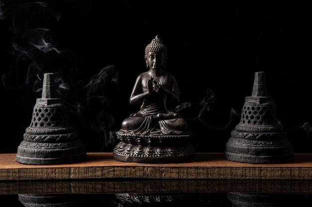 Standbeeld van boeddha zittend in meditatie, met boeddhistische klokken en wierookrook