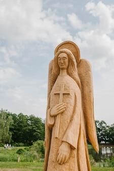 Standbeeld van een engelenboom met vleugels en een kruis