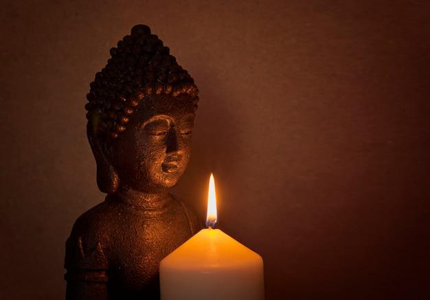 Standbeeld van een heilige boeddha in het licht van een kaars