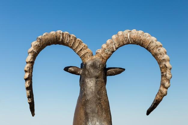 Standbeeld van geit met hoorns met blauwe hemel