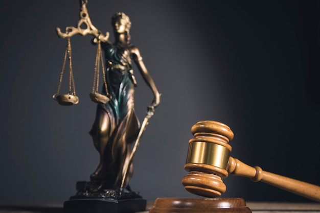 Standbeeld van justitie en hamer op houten tafel