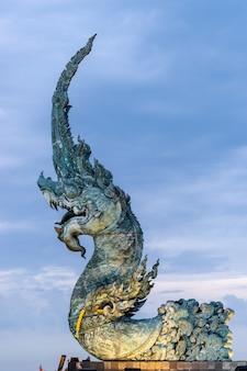 Standbeeld van koning van naga met bewolkte hemel op achtergrond.