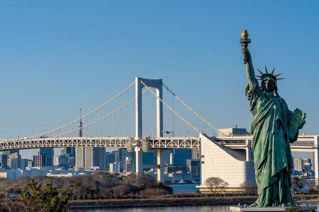 Standbeeld van vrijheid en regenboogbrug, in odaiba tokyo, japan wordt gevestigd dat