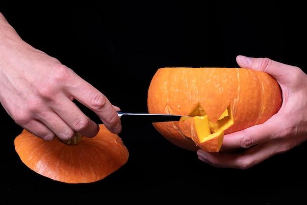 Stap 3 ogen en mond snijden in een pompoen met een mes om jack's lantaarn voor te bereiden, geïsoleerd op zwarte achtergrond, close-up, kopieer ruimte. stapsgewijze instructies voor het maken van jack's lantaarn