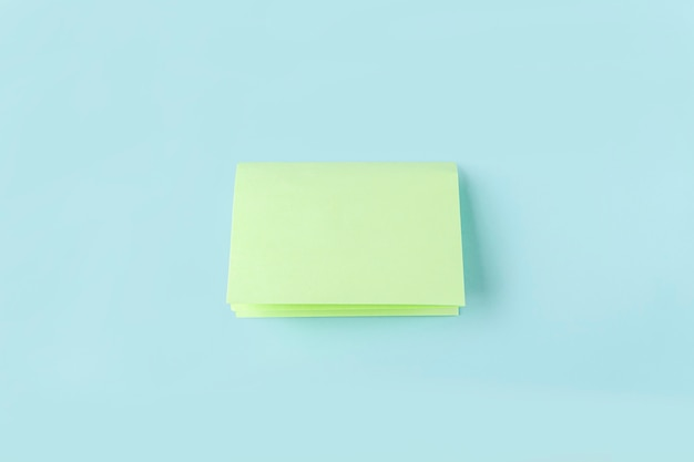 Stap drie om een vlinder van origamipapier te maken met groen papier, een schaar op een blauwe achtergrond