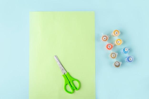 Stap één van hoe je een vlinder van origamipapier maakt met groen papier, een schaar op een blauwe achtergrond