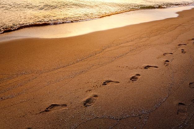 Stap voetafdrukken op het zandstrand in de ochtend