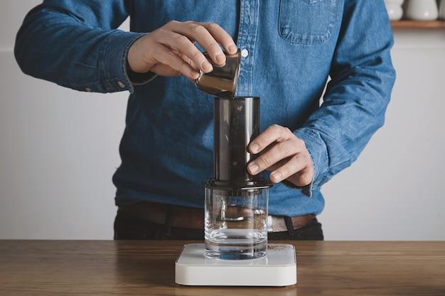 Stap voor stap aero pers koffiebereiding barista in spijkerbroek shirt giet gemalen koffiepoeder van stalen beker naar aeropress professionele koffiebrouwerij caféwinkel