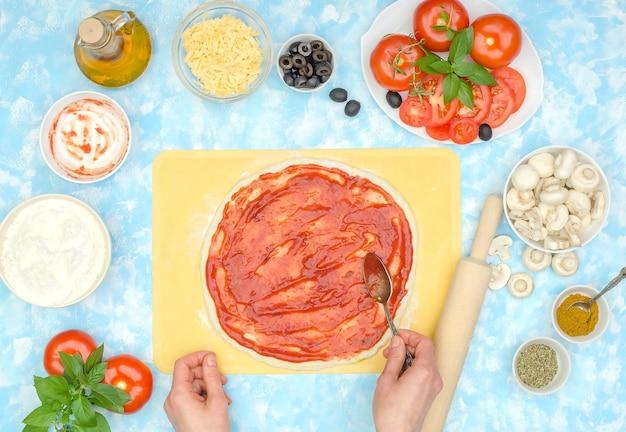 Stap voor stap bereiding van zelfgemaakte vegetarische pizza, stap 3 - tomatensaus op het deeg smeren