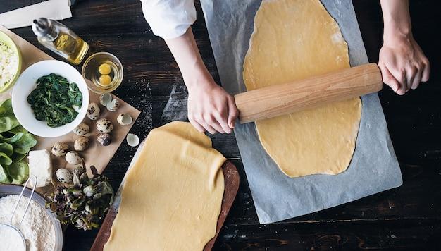 Stap voor stap bereidt de chef-kok ravioli met ricottakaas, dooierkwartelseieren en spinazie met kruiden. de chef werkt met het deeg