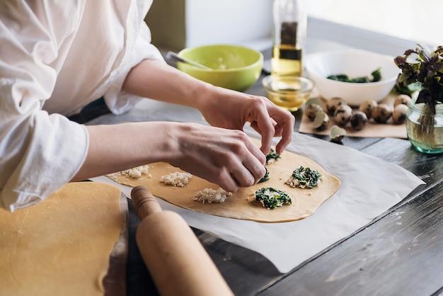 Stap voor stap bereidt de chef ravioli met ricotta kaas, dooiers kwarteleitjes en spinazie met kruiden. de chef bereidt de vulling op het deeg