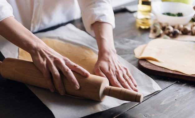 Stap voor stap bereidt de chef ravioli met ricotta kaas, dooiers kwarteleitjes en spinazie met kruiden. de chef werkt met het deeg