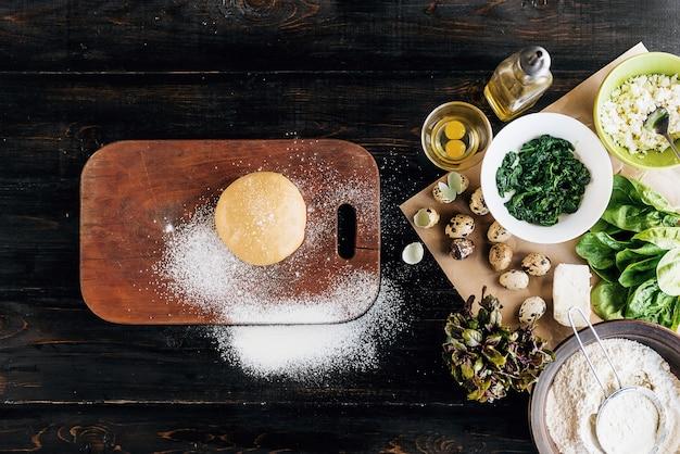 Stap voor stap bereidt de chef ravioli met ricotta kaas, dooiers kwarteleitjes en spinazie met kruiden. een set producten voor ravioli