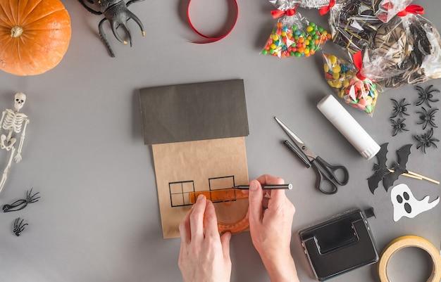 Stap voor stap een cadeau voor halloween inpakken, met behulp van een liniaal twee vensters van de gewenste vorm tekenen met een viltstift