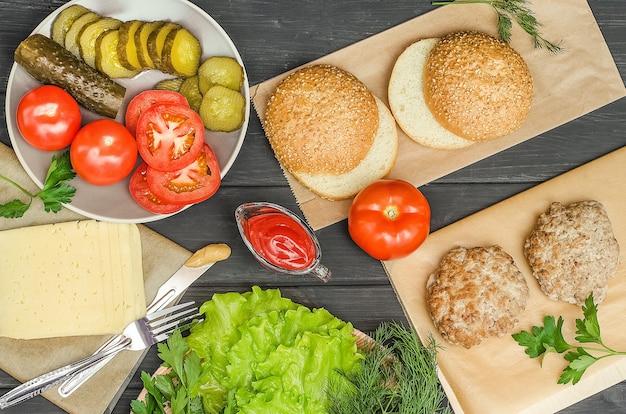 Stap voor stap een hamburger koken, stap 1 - de ingrediënten klaarmaken op een zwarte achtergrond.