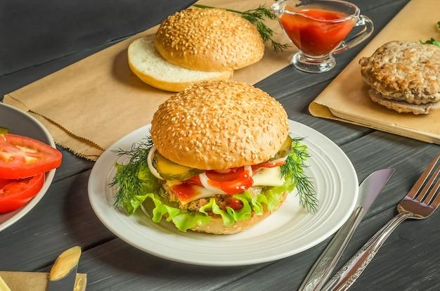 Stap voor stap een hamburger koken, stap 11 - klaar hamburger op een bord op een zwarte achtergrond