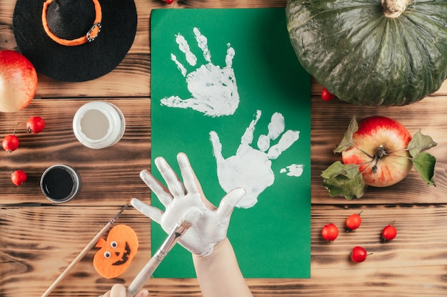 Stap-voor-stap halloween tutorial geesten handafdruk van het kind. stap 5: kind brengt met penseel witte verf aan op handpalm. bovenaanzicht