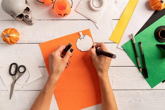 Stap voor stap instructie voor het maken van halloween-bladwijzer diy-pompoenambachten. stap 3 - teken een pompoenvorm op een stuk papier of vilt