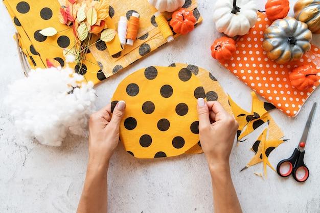 Stap voor stap instructie voor het maken van halloween-textiel diy-pompoenambacht. stap 2 - een cirkel uit textiel snijden. bovenaanzicht plat lag