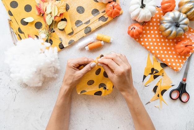 Stap voor stap instructie voor het maken van halloween-textiel diy-pompoenambacht. stap 3 - een cirkel rond naaien en vastbinden. bovenaanzicht plat lag