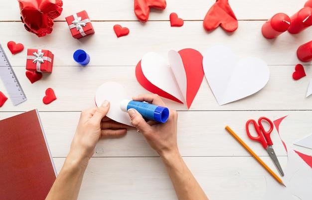 Stap voor stap instructie voor het maken van papieren hartvormige luchtballon. stap 5 - lijm witte kanten van harten aan elkaar zodat ze een dimensionaal hart vormen