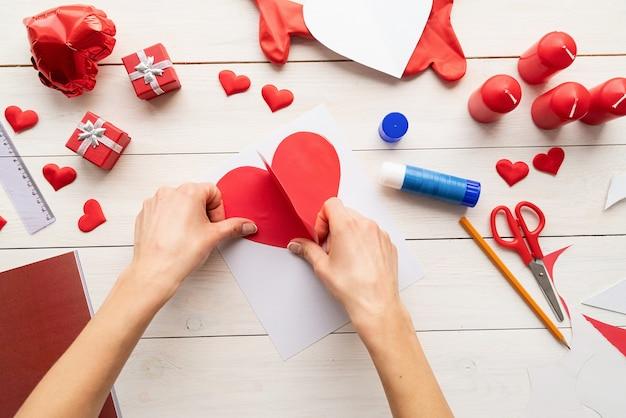 Stap voor stap instructie voor het maken van papieren hartvormige luchtballon. stap 6 - lijm het grote hart op een stuk hard papier en laat er wat ruimte onder Premium Foto