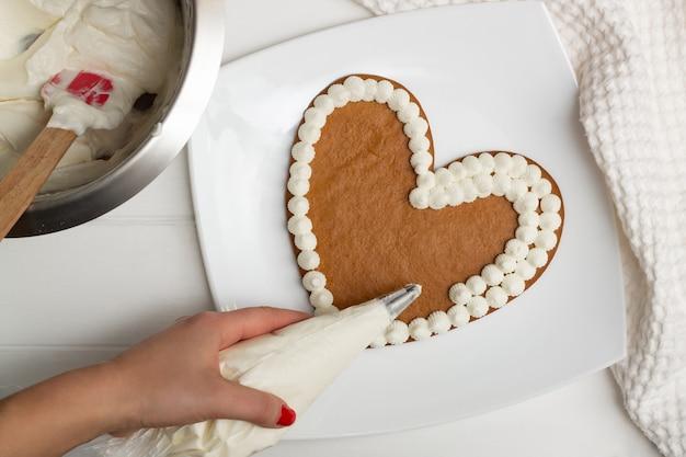 Stap-voor-stap instructies voor hartvormige taartrecepten. stap 10: breng de crème aan op de cakes met een spuitzak, plat gelegd.