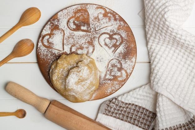 Stap-voor-stap instructies voor hartvormige taartrecepten. stap 3. bloem en zout toevoegen, het deeg kneden, plat leggen.