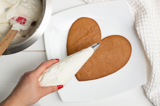 Stap-voor-stap instructies voor hartvormige taartrecepten. stap 9: doe de room in een spuitzak, plat neergelegd.