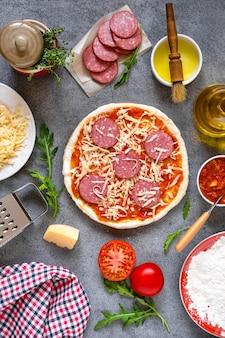 Stap voor stap maakt een pizza-margarita. deeg en pizza-ingrediënten. italiaanse pizza koken op donker tafelblad.