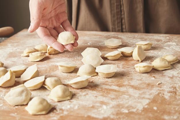 Stap voor stap maken van zelfgemaakte dumplings, ravioli of pelmeni met gehaktvulling met behulp van ravioli-vorm of ravioli-maker. klaar voor het koken van ravioli op een houten bord, houdt de vrouwenhand er een