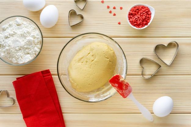 Stap voor stap recept voor het maken van koekjes voor valentijnsdag. afgewerkt zandkoekdeeg in een glazen kom