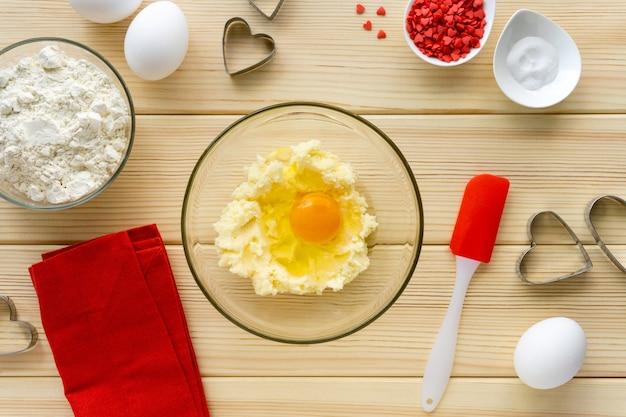 Stap voor stap recept voor het maken van koekjes voor valentijnsdag. zoete botermengsel en ei in glazen kom op houten tafel.