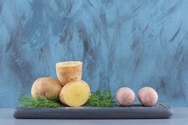 Stapel aardappelen liggend op zwarte houten planken.