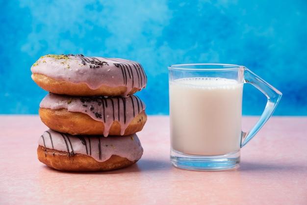 Stapel aardbei donuts en een glas melk op roze tafel.
