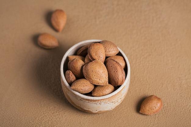 Stapel amandelnoten in een kom op een bruin oppervlak. verse noten in hun schelpen.
