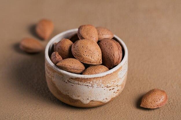 Stapel amandelnoten in een kom op een bruine achtergrond. verse noten in hun schelpen.